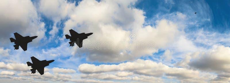 Silhuetas de três aviões F-35 contra o céu azul fotografia de stock