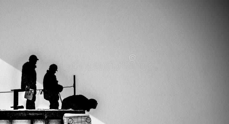 Silhuetas de três construtores em um fundo preto e branco imagens de stock royalty free