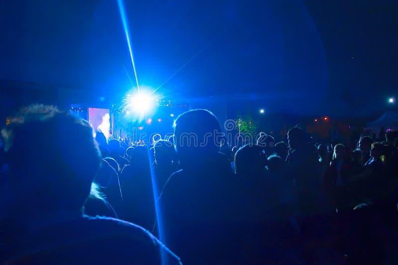 Silhuetas de um grande número povos no fundo dos projetores Conceito: celebração, reunião fotos de stock