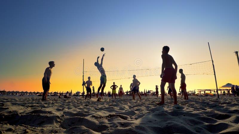 Silhuetas de um grupo de jovens que jogam o voleibol de praia foto de stock royalty free