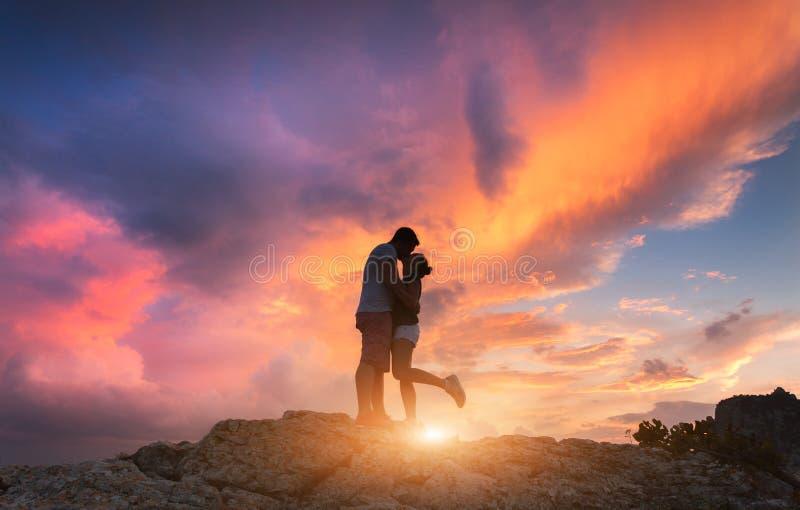 Silhuetas de um homem e de uma amiga de aperto e de beijo foto de stock royalty free