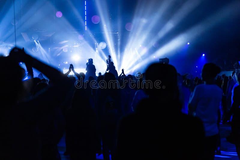 Silhuetas de uma multidão do concerto e de um operador cinematográfico na perspectiva dos raios brilhantes, coloridos na fase fotografia de stock royalty free