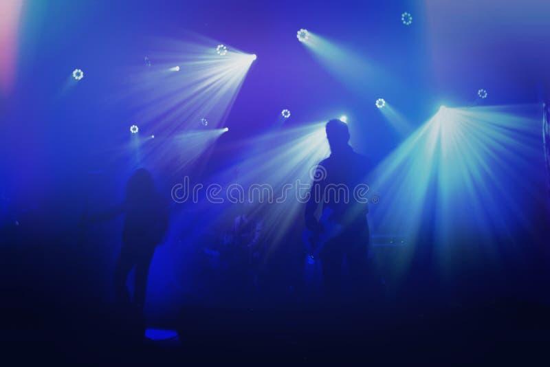 Silhuetas do grupo de rock na fase no concerto imagens de stock royalty free