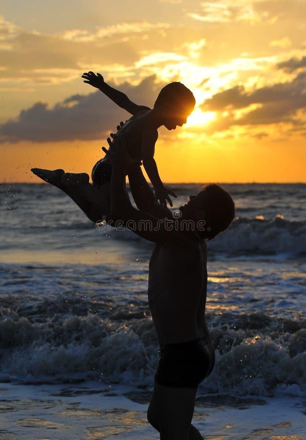 Silhuetas do homem e da criança na praia foto de stock