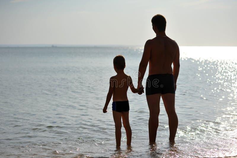 Silhuetas do homem e da criança que estão na água foto de stock
