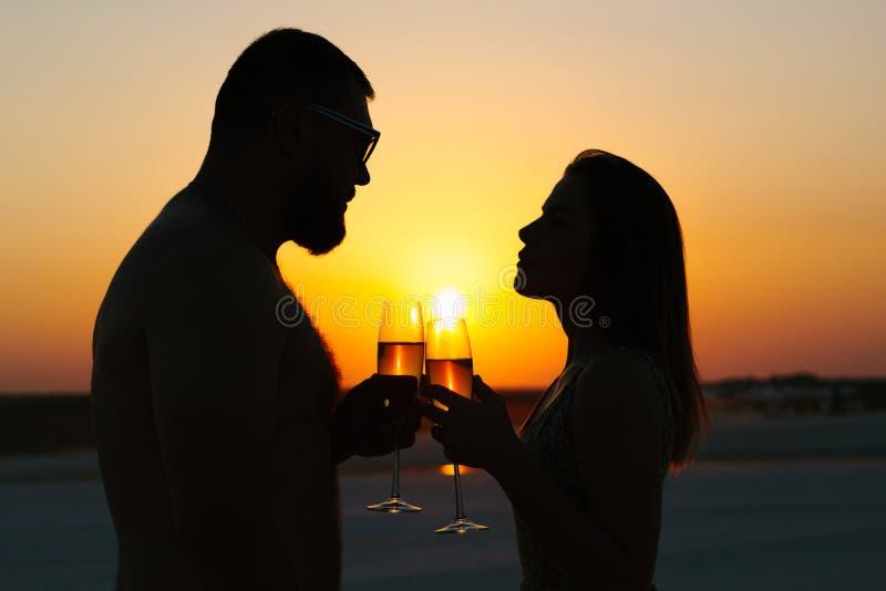 Silhuetas do homem e da mulher, par feliz no amor na praia fotos de stock royalty free
