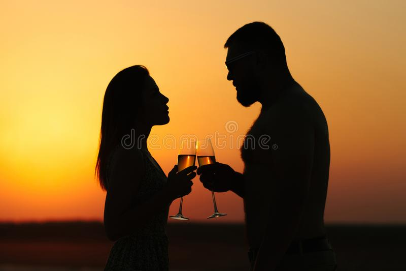 Silhuetas do homem e da mulher, par feliz no amor na praia no por do sol, olhando-se, sorrindo e realizando em seu ha imagens de stock