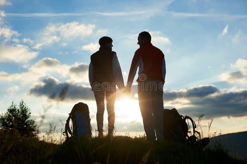 Silhuetas do homem e da mulher que olham se, mantendo as mãos contra o por do sol nas montanhas fotografia de stock royalty free