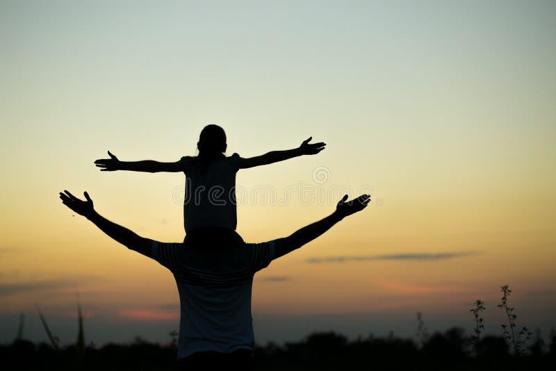 Silhuetas do pai e da filha em seus ombros com mãos acima de ter o divertimento, contra o céu do por do sol parenthood fotografia de stock
