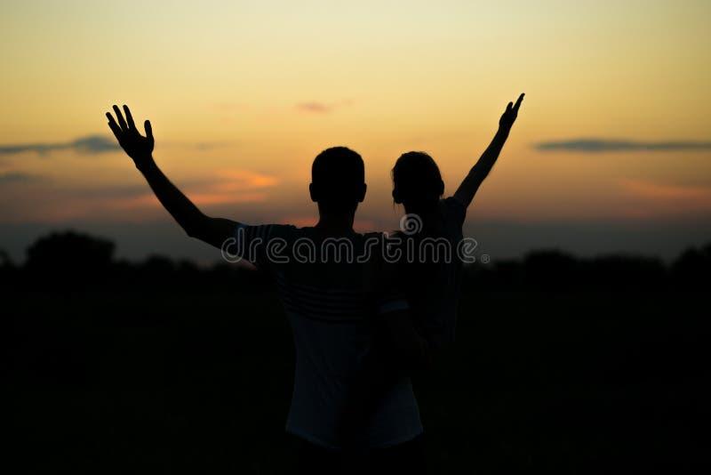 Silhuetas do pai e da filha em seus ombros com mãos acima de ter o divertimento, contra o céu do por do sol parenthood fotografia de stock royalty free