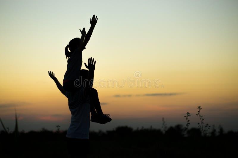 Silhuetas do pai e da filha em seus ombros com mãos acima de ter o divertimento, contra o céu do por do sol imagens de stock