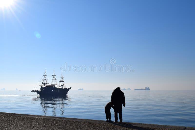 Silhuetas do pai e do filho na frente do golfo de Thermaikos, Tessalónica Grécia Barco azul do mar e de navigação na névoa fotos de stock royalty free