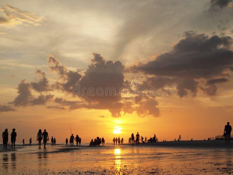 Silhuetas do por do sol da praia de passeio dos povos imagem de stock royalty free