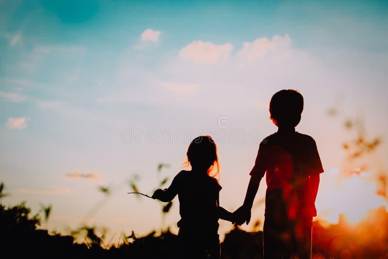 Silhuetas do rapaz pequeno e da menina que guardam as mãos no por do sol imagem de stock royalty free