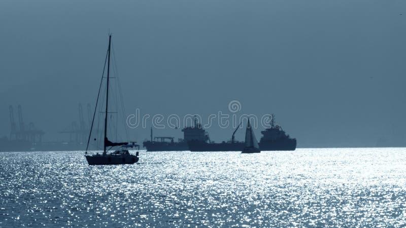Silhuetas do veleiros e navios de carga desconhecidos perto de Gibraltar fotografia de stock