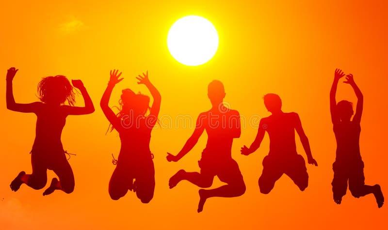 Silhuetas dos adolescentes e das meninas que saltam altamente no ar sobre