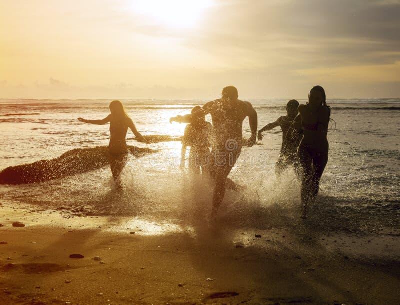 Silhuetas dos amigos que correm fora do oceano imagens de stock royalty free