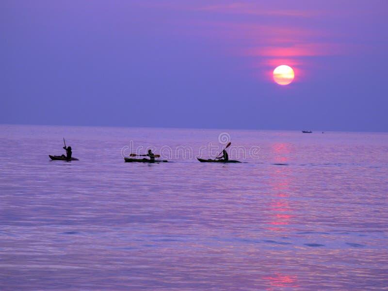 Silhuetas dos kayakers no por do sol da Índia fotografia de stock