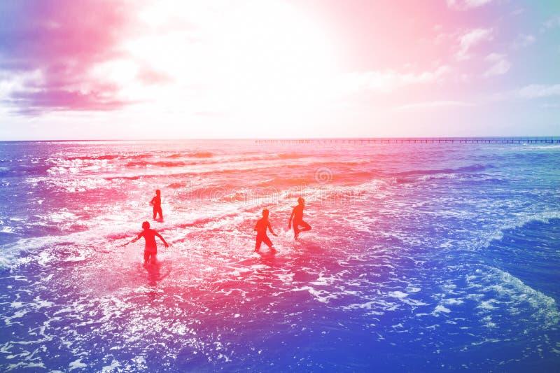 Silhuetas dos meninos que correm ao mar fotos de stock