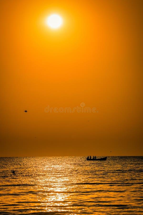 Silhuetas dos pescadores no mar em uma pesca do barco no mornin fotografia de stock royalty free