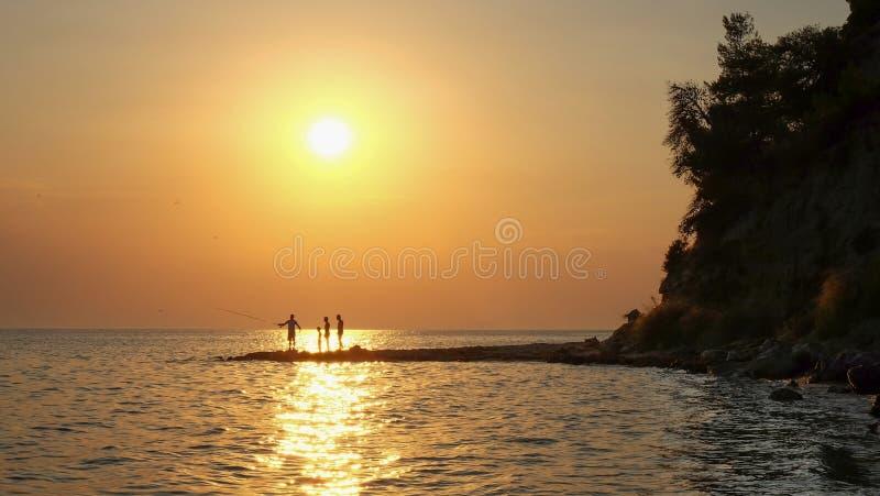Silhuetas dos pescadores que pescam no beira-mar fotos de stock royalty free