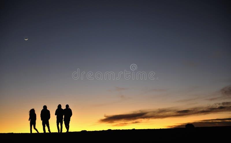 Silhuetas dos povos de encontro ao céu nocturno fotos de stock royalty free