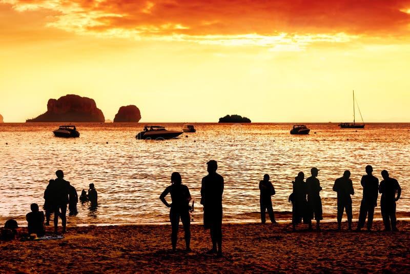 Silhuetas dos povos desconhecidos que olham o por do sol vermelho imagens de stock