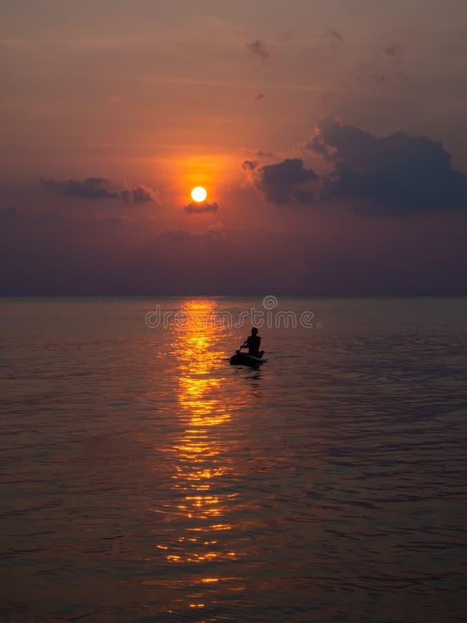 Silhuetas dos povos em um caiaque nos raios do sol de ajuste na perspectiva das nuvens fotografia de stock
