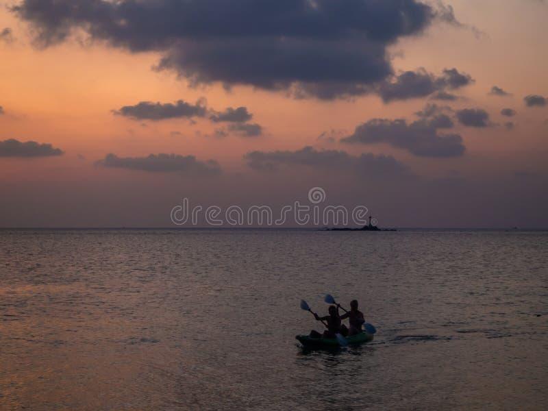 Silhuetas dos povos em um caiaque nos raios do sol de ajuste na perspectiva das nuvens imagem de stock royalty free