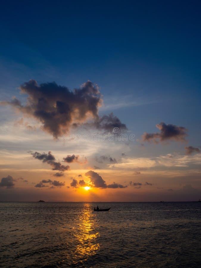 Silhuetas dos povos em um caiaque nos raios do sol de ajuste na perspectiva das nuvens foto de stock