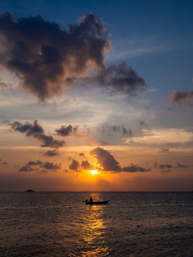 Silhuetas dos povos em um caiaque nos raios do sol de ajuste na perspectiva das nuvens fotografia de stock royalty free