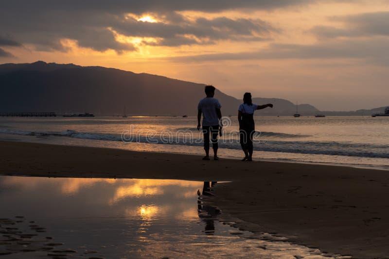 Silhuetas dos povos no fundo de um alvorecer na praia de Sanya, ilha de Hainan, China imagem de stock