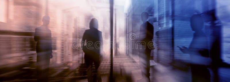 Silhuetas dos povos que andam na rua perto dos arranha-céus e dos prédios de escritórios modernos Imagem borrada da exposição múl imagens de stock