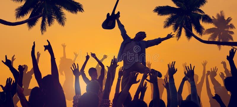 Silhuetas dos povos que apreciam um concerto na praia foto de stock royalty free