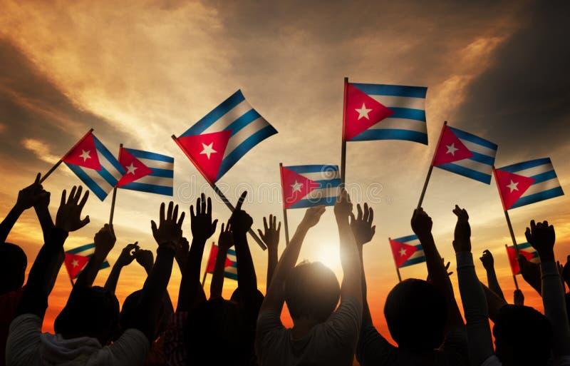Silhuetas dos povos que guardam a bandeira de Cuba imagem de stock