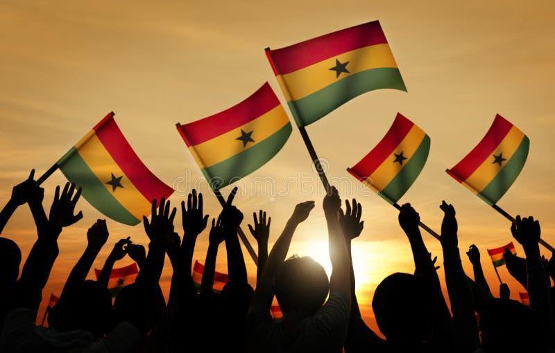 Silhuetas dos povos que guardam a bandeira de Gana imagem de stock royalty free