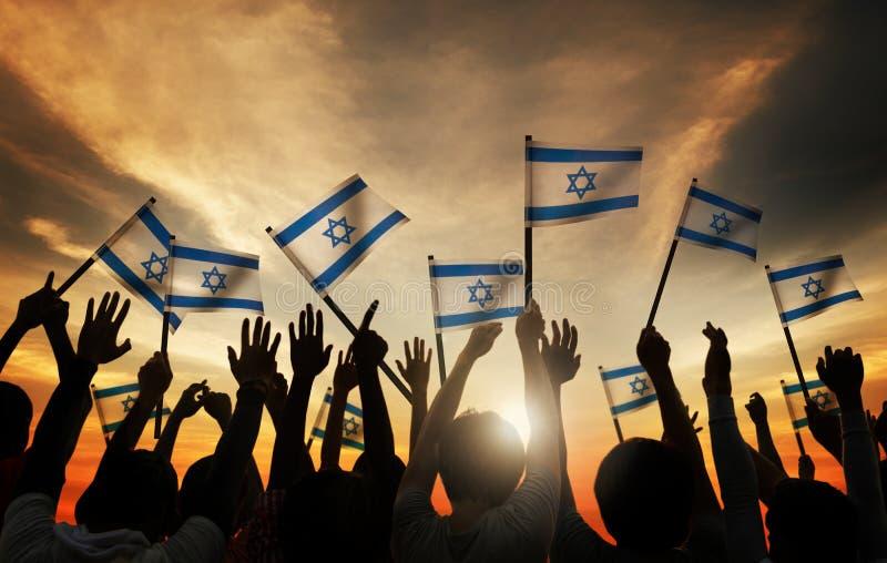 Silhuetas dos povos que guardam a bandeira de Israel imagens de stock royalty free