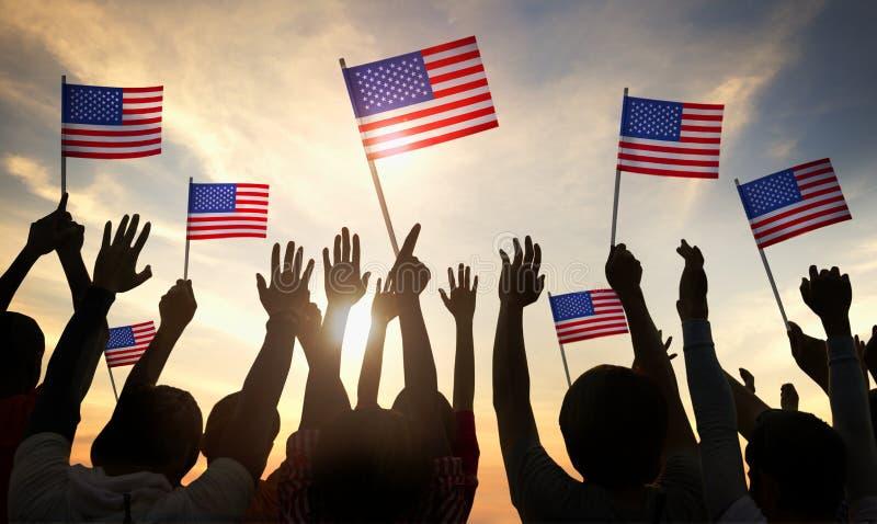 Silhuetas dos povos que guardam a bandeira dos EUA foto de stock royalty free