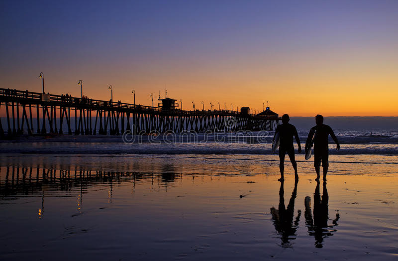 Silhuetas dos surfistas na praia imperial Pier Sunset foto de stock