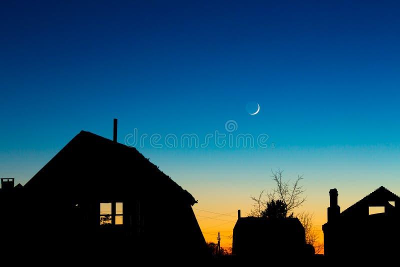 Silhuetas dos telhados contra o céu noturno com novo foto de stock royalty free