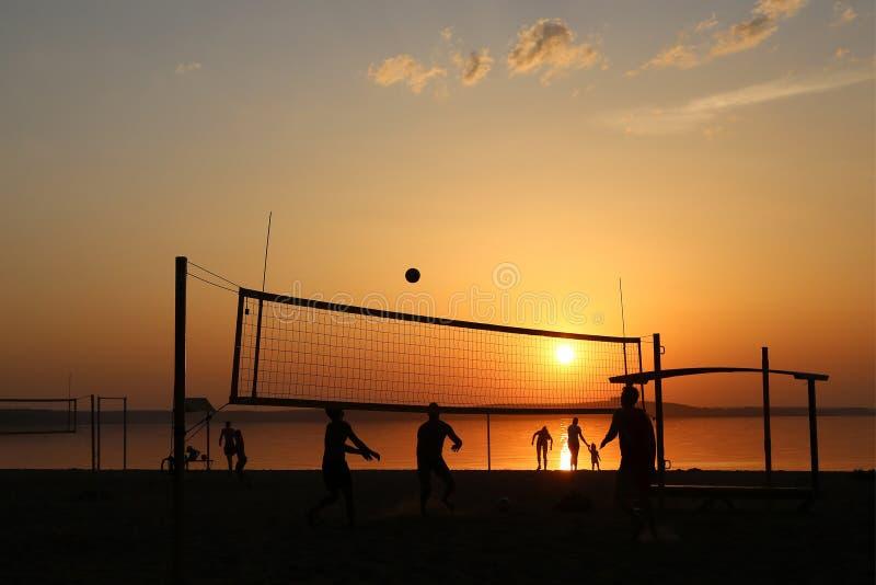 Silhuetas na praia ao jogar o voleibol no por do sol fotografia de stock