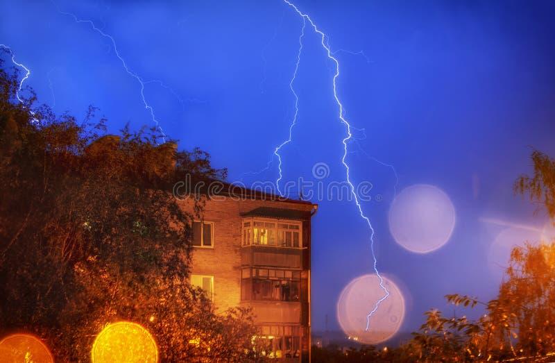 Silhuette av åskvigg över byggnaderna och waterdropsna royaltyfri foto