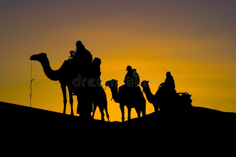 Silhuette Of A Camel Caravan In The Desert Stock Images