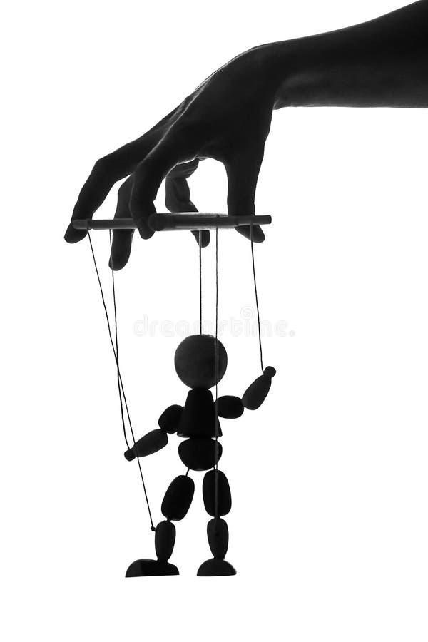 Silhuette da boneca em cordas Mão fêmea que manipula um fantoche fotografia de stock royalty free