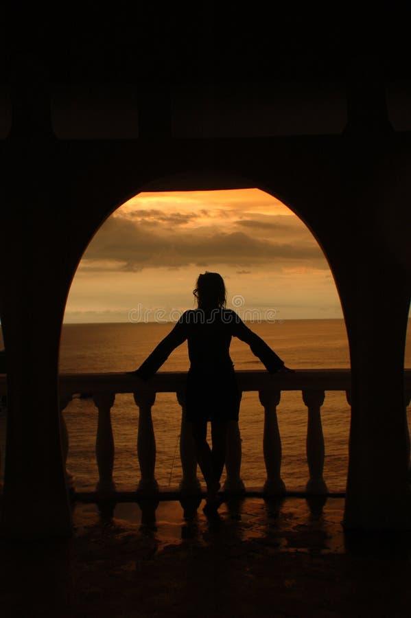 Silhuette del mujeres en un arco contra una puesta del sol tropical hermosa imagen de archivo