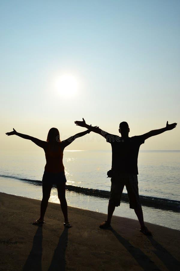 Silhuette di una coppia sulla spiaggia immagini stock libere da diritti