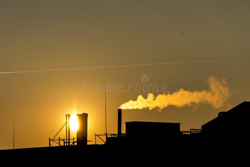 Silhuette fabryki Przemysłowy dym od smokestacks nad kolorowym zmierzchu nieba przemysłem zdjęcia royalty free