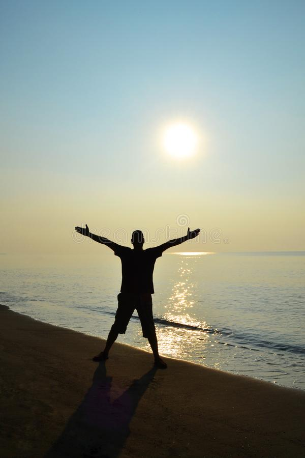 Silhuette of a man on the beach. Silhuette of a man having fun with sunrise on the beach stock photography