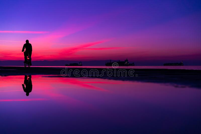 Silhuette of Man on Bicycle and his reflection on water from rain, against Lovely Colors Sky in Purple and Blue Tones stock photos