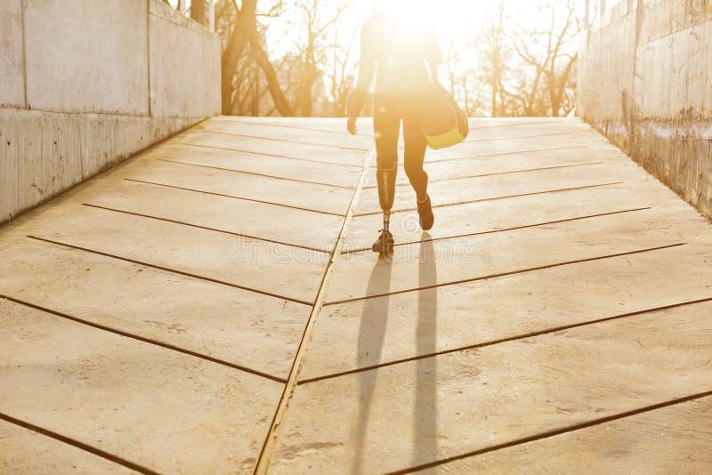Silhuette van zonovergoten atletisch gehandicapt meisje met prothetisch been i stock afbeelding